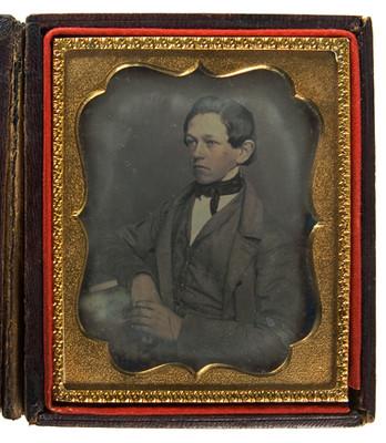 Hombre adolescente sentado y recargado junto a una mesa, retrato de tres cuartos de perfil