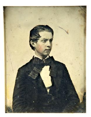 Niño porta traje con corbata en moño, retrato