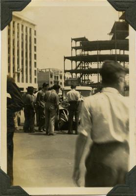 Hombres observan automóvil chocado junto al edificio de la Lotería Nacional