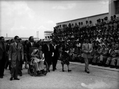 Antonio Ruiz Galindo en silla de ruedas, caminando con su esposa e hija y otras personas, pasando fente al público, probablemente durante ua ceremonia