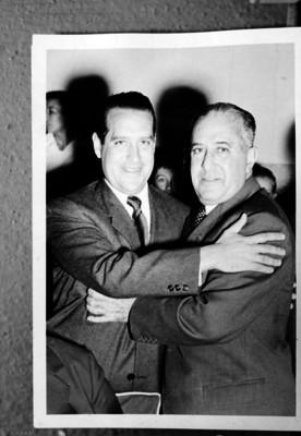 Antonio Ruiz Galindo, Secretario de Economia, es abrazado por un hombre, durante un evento, retrato