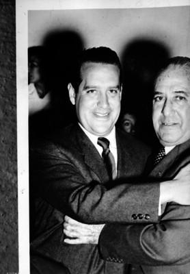 Antonio Ruiz Galindo, recibe el abrazo de un hombre, durante un evento, retrato