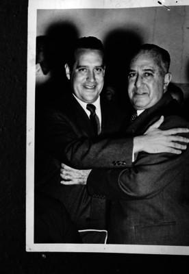 Antonio Ruiz Galindo es abrazado por un hombre, durante un evento, retrato