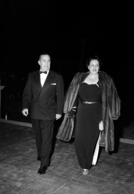 Antonio Ruiz Galindo y esposa vestidos elegantemente, caminado en un salón; durante un evento social.