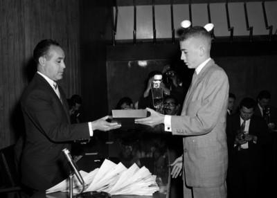 Antonio Ruiz Galindo, entregando un reconocimiento a un hombre, durante una ceremonia en un salón