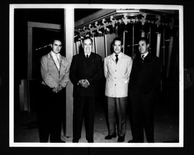 Antonio Ruiz Galindo acompañado de hombres dentro de la fábrica DM Nacional, retrato de grupo