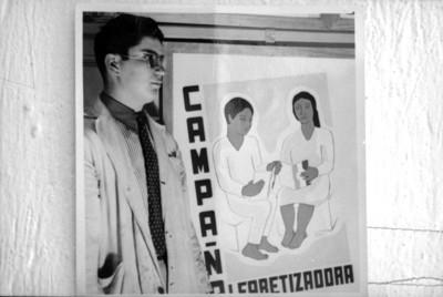 Alfonso Soto Soria junto a un cartel del proyecto de la Escuela Libre de Arte y Publicidad sobre una campaña alfabetizadora, reprografía