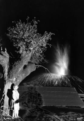 """Mujer junto a una casa observa la erupción """"El Paricutín"""", toma nocturna"""