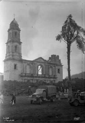 "Gente con camiones frente a la iglesia de ""San Juan"" rodeada por material volcánico"