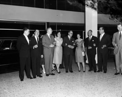 Ejecutivos y mujeres en una agencia automotriz