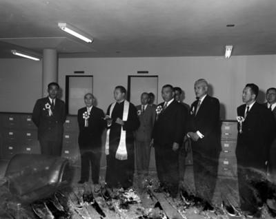 Sacerdote y hombres en oficina de la fábrica Toyoda