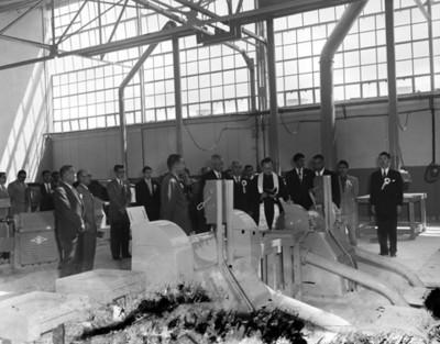 Sacerdote y hombres ante maquinaria de la fábrica Toyoda
