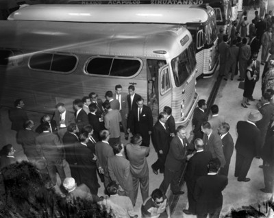 Gente entre autobuses esestacionados