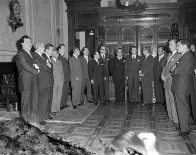 Hombres esperan en un salón, retrato de grupo