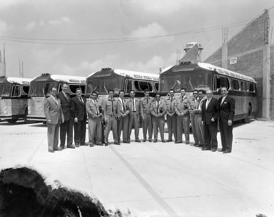 Choferes y ejecutivos parados frente autobuses en una central camionera, retrato de grupo