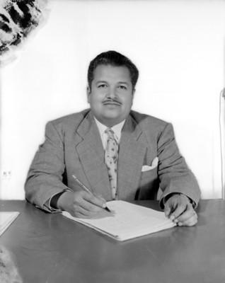 Hombre revisa documentos en escritorio, retrato