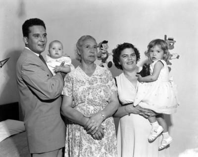 Pareja y anciana con niñas en habitación, retrato de grupo