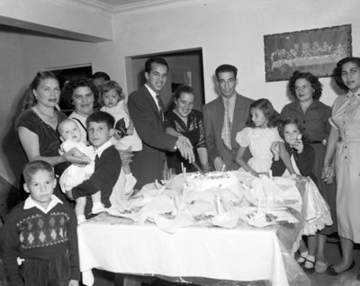 Hombre parte pastel durante festejo familiar