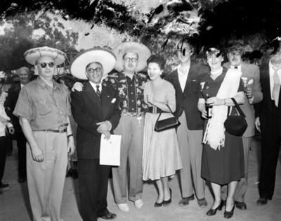 Personas portan sombreros regionales en plaza pública, retrato de grupo
