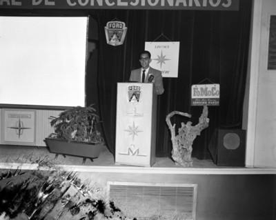 Hombre pronuncia discurso durante convención de concesionarios Ford