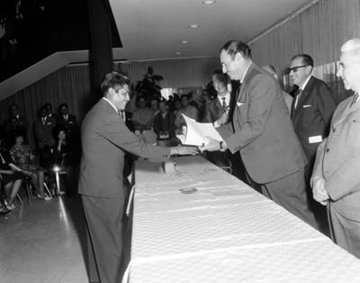 Ejecutivo entrega documentos a empleado en salón durante ceremonia