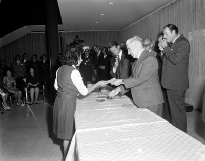 Ejecutivo entrega documento a empleada en un salón durante ceremonia