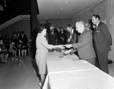 Ejecutivo entrega documento a empleada durante ceremonia en un salón