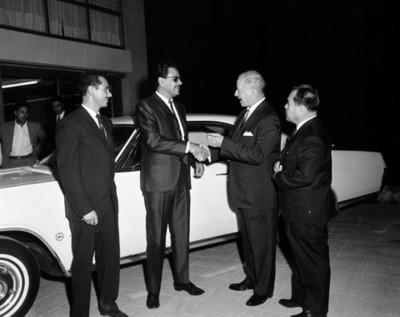 Ejecutivo le entrega llave de automóvil a un hombre en agencia automotríz