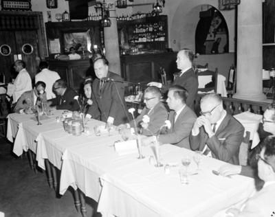 Hombre pronuncia discurso desde comedor durante banquete