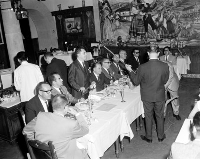 Hombres instalan micrófono ante comedor durante banquete