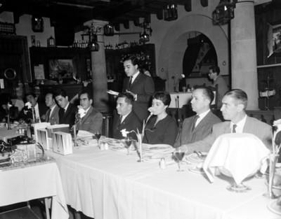 Hombre y mujer en mesa principal durante banquete en un restaurante