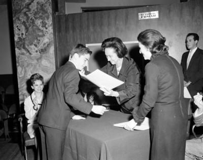 Eva Samano de López Mateos entrega documento a niño en un auditorio