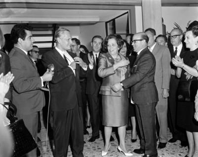 Guadalupe Borja de Díaz Ordaz es felicitada por un hombre durante reunión en un salón