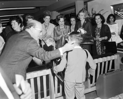 Guadalupe Borja de Díaz Ordaz aplaude a niño que toca el acordeón durante avento en un salón