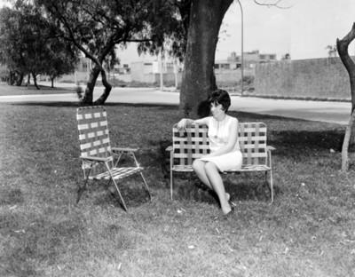 Mujer sentada en silla plegable en un parque, retrato