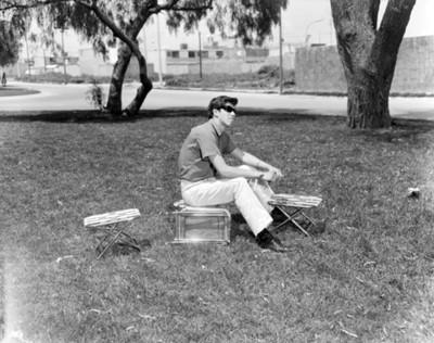 Hombre sentado sobre un banco en parque, retrato