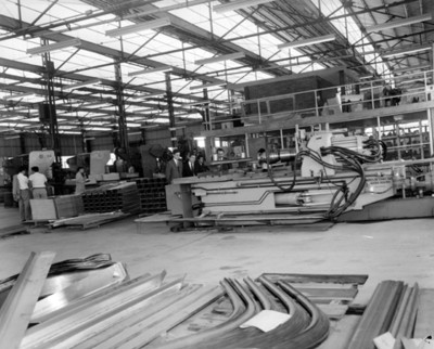 Ejecutivos observan funcionamiento de máquina en una fábrica automotríz