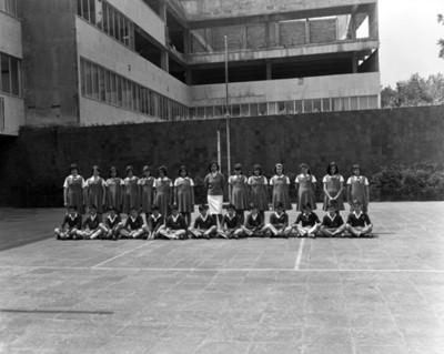 Estudiantes y maestra en patio de escuela, retrato de grupo