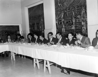 Hombres en comedor durante banquete en salón