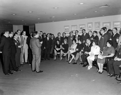 Hombre pronuncia discurso a ejecutivos y mujeres durante reunión en un salón