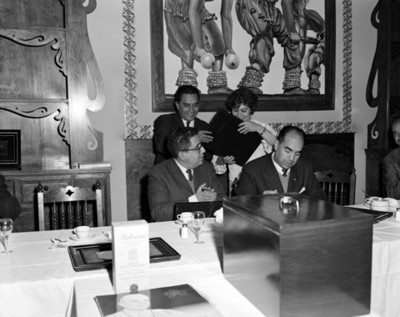 Directivos entregan reconocimiento a hombres durante banquete