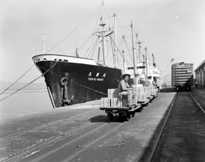 Trabajadores sentados sobre mercancía en embarcadero del puerto de Acapulco