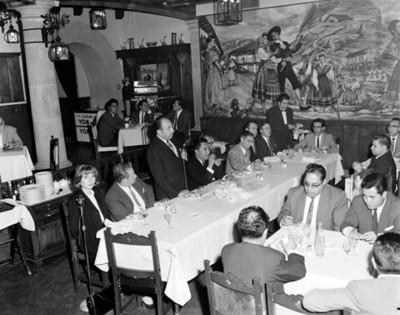 Hombre con microfóno pronuncia a los asistentes al banquete en un restaurante