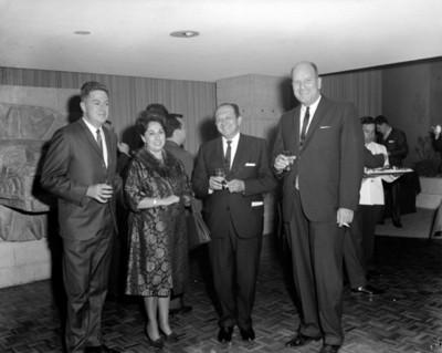 Ejecutivos con bebida en mano y mujer durante inauguración de agencia automotríz, retrato de grupo