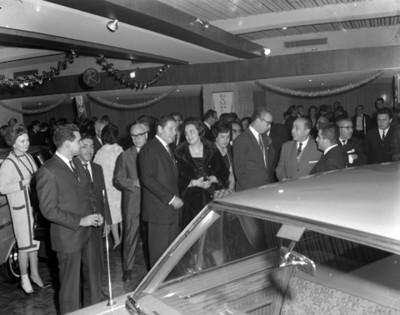 Ejecutivos observan auto nuevo durante inauguración de agnecia automotríz