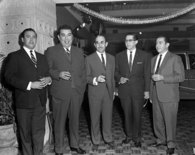 Ejecutivos de pie con bebida en mano durante inauguración de una agencia automotríz