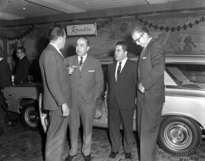 """Ejecutivos de pie platican junto a un automóvil """" rambler"""" durante inauguración de una agencia automotríz"""