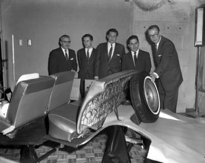Ejecutivos observan asientos y llanta de automóvil durante inauguración de agencia automotríz