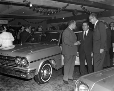 """Ejecutivos platican junto a un automóvil """" RAMBLER"""" durante inauguración de una agencia automotríz"""