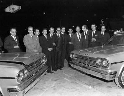 """Ejecutivos reunidos junto a automóviles """" RAMBLER"""" durante la inaugurción de una agencia automotríz"""